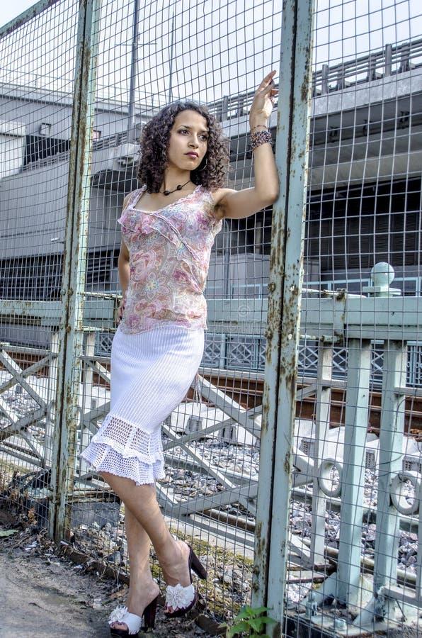Piękna młoda Afrykańska oliwkowa kobieta w lato sukni w przemysłowym terenie zdjęcie royalty free