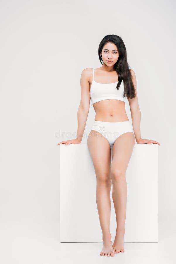 piękna młoda amerykanin afrykańskiego pochodzenia kobieta pozuje w bieliźnie blisko białego sześcianu zdjęcie stock