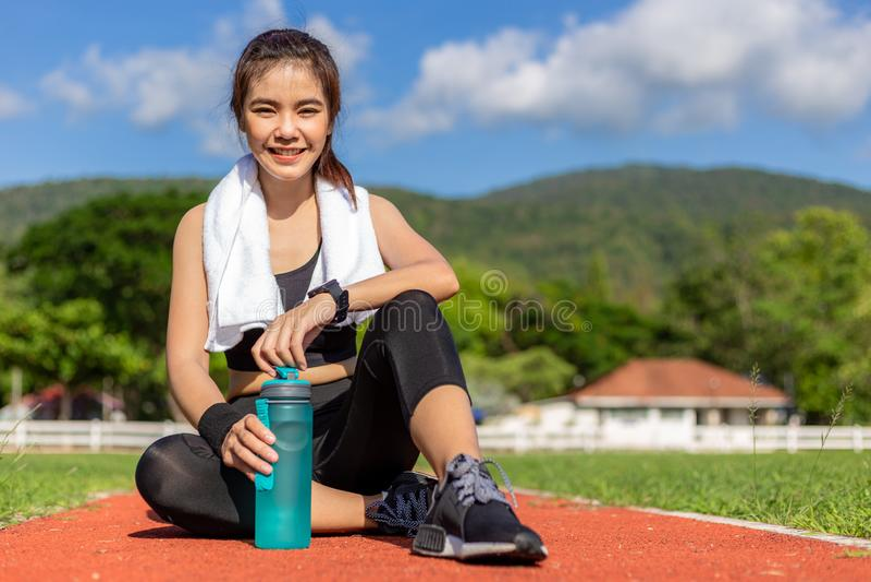 Piękna młoda Azjatycka kobieta w sprawność fizyczna stroju obsiadaniu na bieg śladzie i ono uśmiecha się przy kamerą przy plenero obrazy royalty free