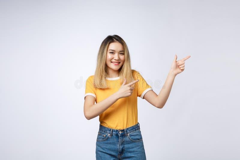 Piękna młoda Azjatycka kobieta wskazuje jej palec z w górę rozochoconego wyrażenia na białym tle, obraz stock