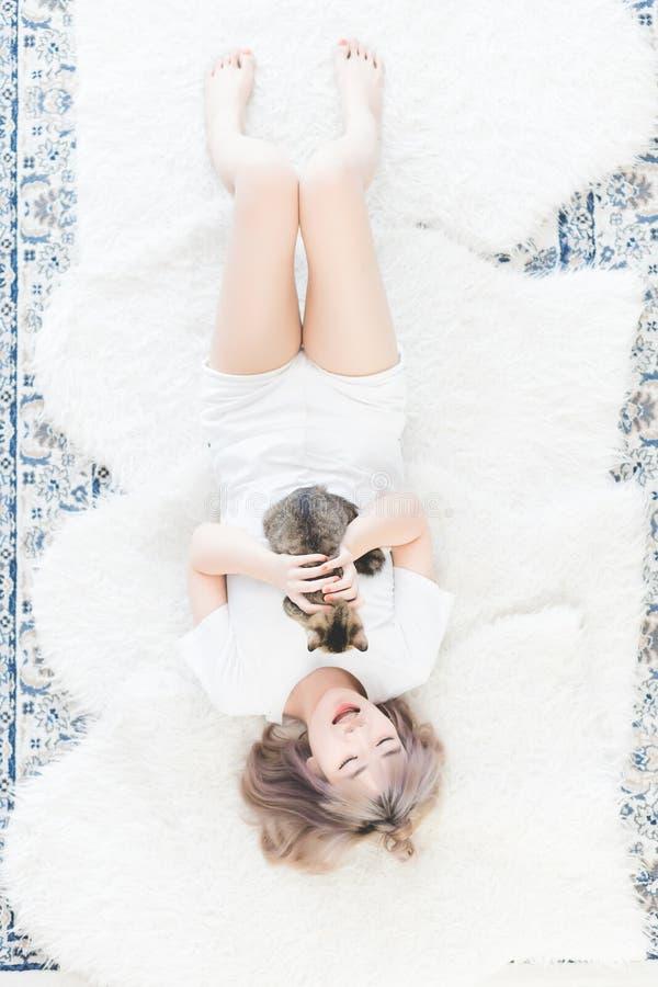Piękna młoda Azjatycka Tajlandzka kobieta kłamał na łóżku z jego kotem szczęśliwie i muskał kot głowę z miłością obraz royalty free