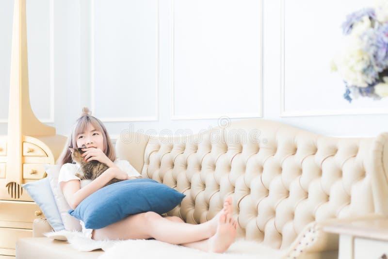 Piękna młoda Azjatycka Tajlandzka kobieta kłamał na kanapie z jego kotem szczęśliwie i muskał kot głowę z miłością obrazy stock