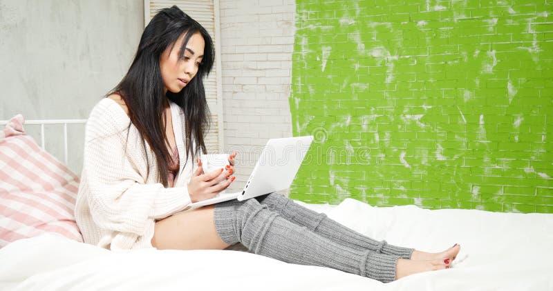 Piękna młoda azjatykcia dziewczyna relaksuje w łóżku, obrazy royalty free