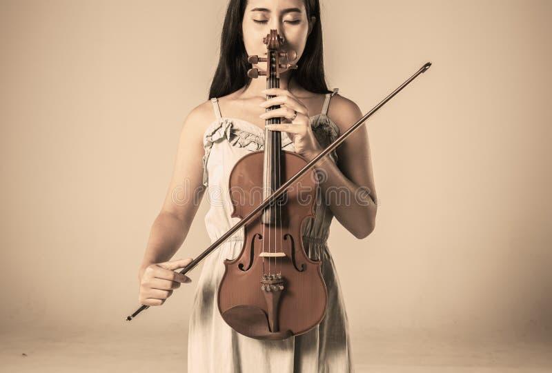 Piękna młoda azjatykcia kobieta bawić się skrzypce fotografia stock