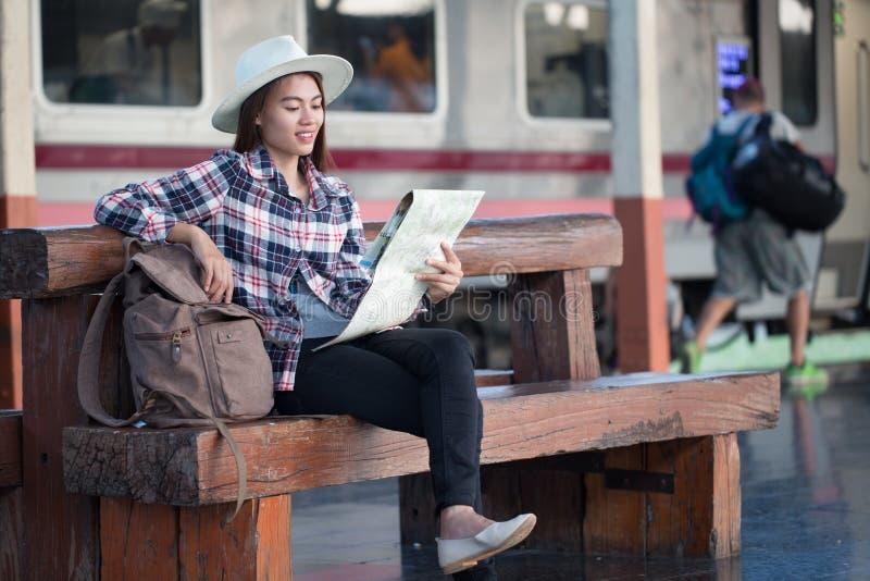 Piękna młoda azjatykcia kobieta czekać na pociąg przy dworcem, lato podróżą, podróżą i wakacje pojęciem, fotografia stock