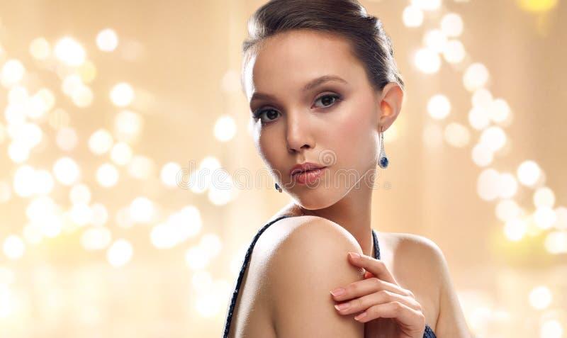 Piękna młoda azjatykcia kobieta jest ubranym kolczyki zdjęcie stock