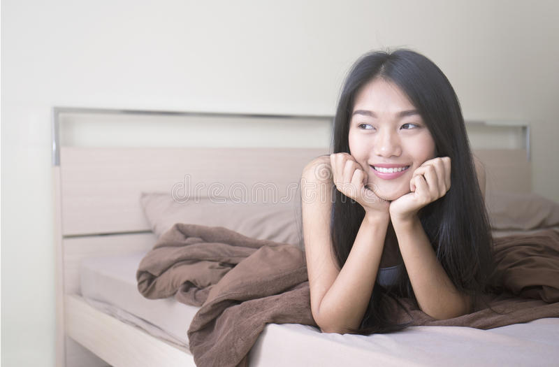 Piękna młoda azjatykcia kobieta kłaść na łóżku obraz royalty free