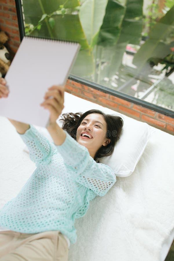 Piękna młoda azjatykcia kobieta kłaść na łóżku i pisze dzienniczku zdjęcia stock