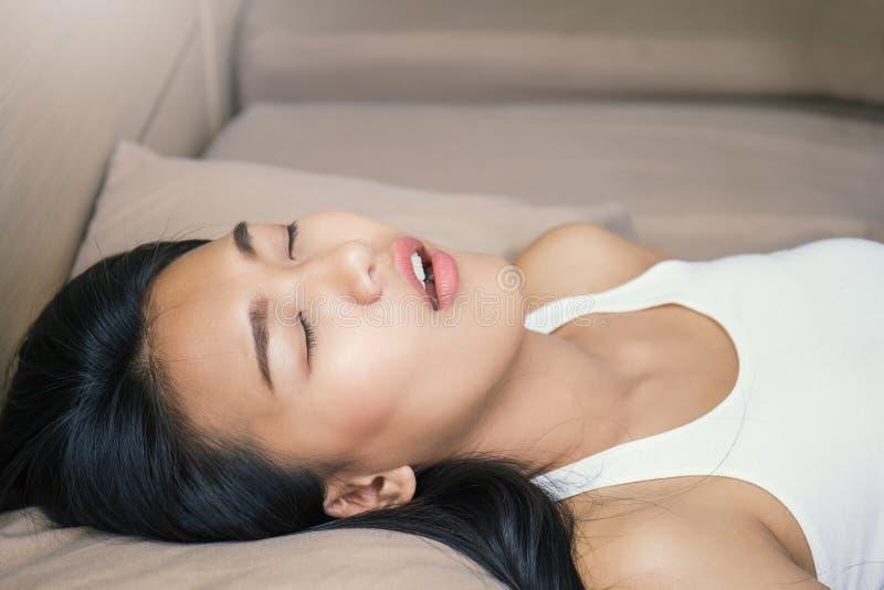 Piękna młoda azjatykcia kobieta kłaść na łóżku z atrakcyjnym uśmiechem obraz stock