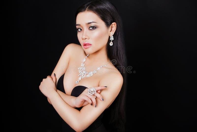 Piękna młoda azjatykcia kobieta pozuje z biżuterią obraz stock