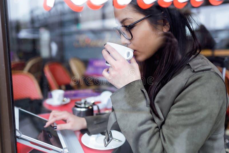 Piękna młoda azjatykcia kobieta używa jej cyfrową pastylkę w sklep z kawą podczas gdy pijący kawę zdjęcie stock