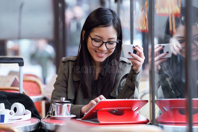 Piękna młoda azjatykcia kobieta używa jej cyfrową pastylkę w sklep z kawą podczas gdy pijący kawę obrazy stock