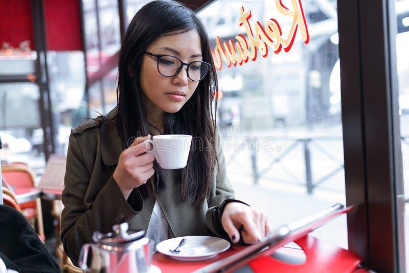 Piękna młoda azjatykcia kobieta używa jej cyfrową pastylkę w sklep z kawą podczas gdy pijący kawę zdjęcia royalty free