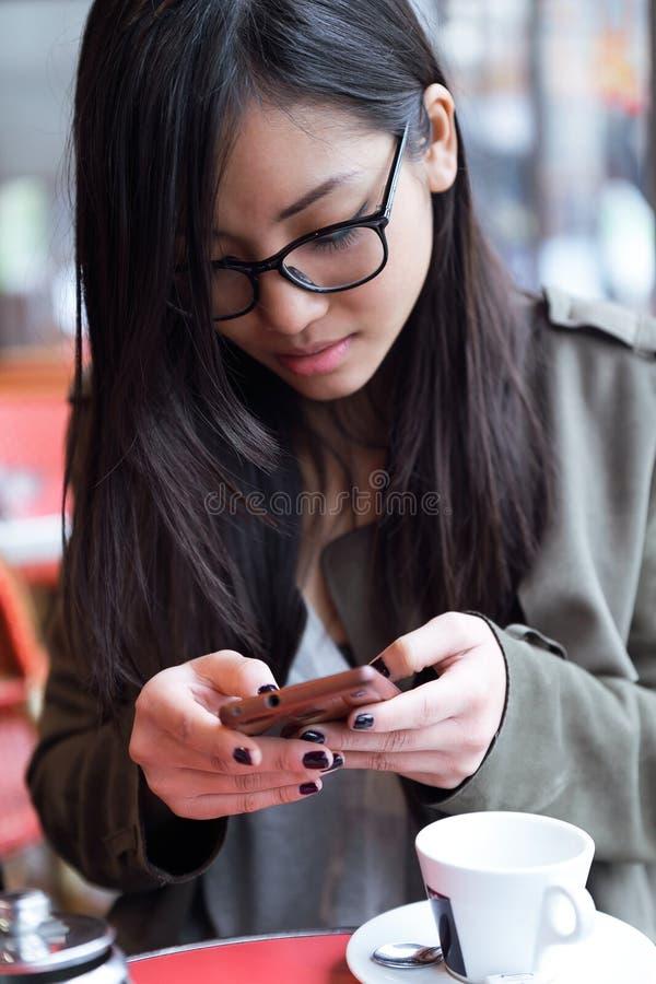 Piękna młoda azjatykcia kobieta używa jej telefon komórkowego w tarasie sklep z kawą zdjęcia royalty free