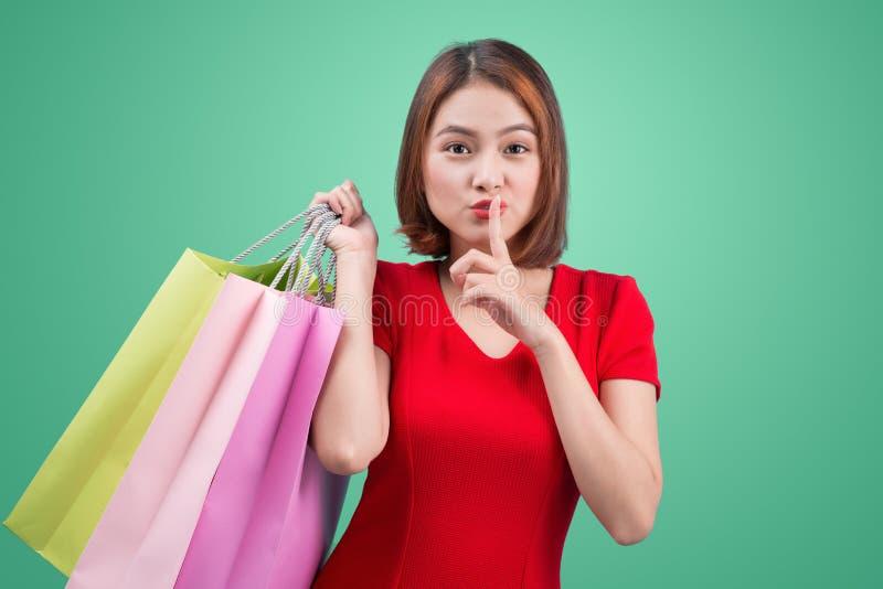 Piękna młoda azjatykcia kobieta z barwionymi torba na zakupy nad błękitem obrazy stock
