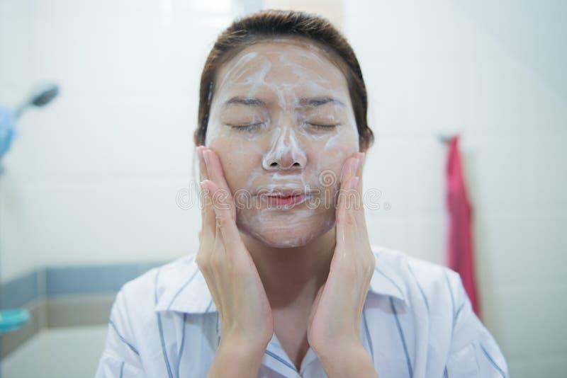 Piękna młoda azjatykcia kobiety cleaning twarzy skóra fotografia stock