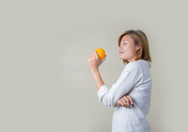 Piękna młoda azjatykcia kobiety mienia pomarańcze na białym tle fotografia royalty free