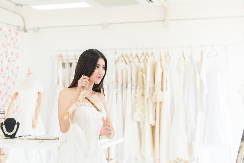Piękna młoda azjatykcia kobiety panna młoda próbuje na ślubnej sukni, Szczęśliwy i uśmiechnięty zdjęcie stock