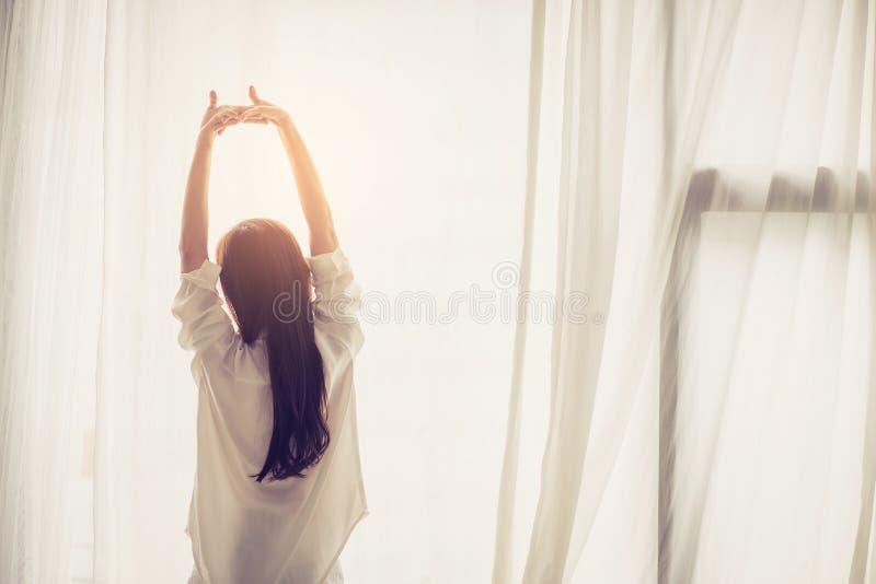 Piękna młoda azjatykcia kobiety rozciągliwość i relaksuje w łóżku po budził się ranek przy sypialnią zdjęcia royalty free