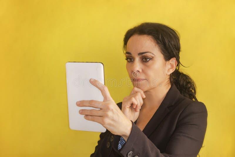 Piękna młoda biznesowa kobieta z pigtail, czarna kurtka, odizolowywająca na tle, patrzeje jej pastylkę zdjęcie stock