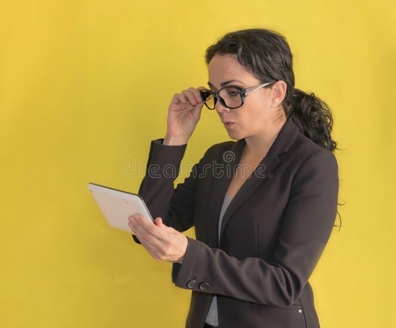 Piękna młoda biznesowa kobieta z szkłami i czarną kurtką, patrzeje jej pastylkę obrazy stock
