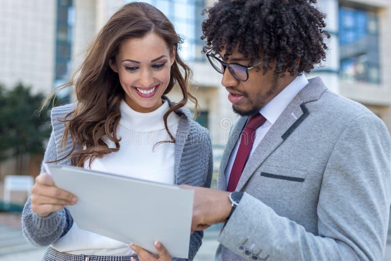 Piękna młoda biznesowa para sprawdza niektóre papierkową robotę przed biurem zdjęcia stock