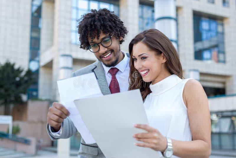 Piękna młoda biznesowa para sprawdza niektóre papierkową robotę przed biurem zdjęcia royalty free
