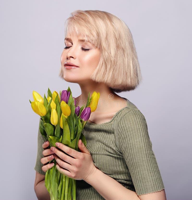 Piękna młoda blondynki dziewczyna oddycha perfumowanie wiosna kwiaty zdjęcie royalty free