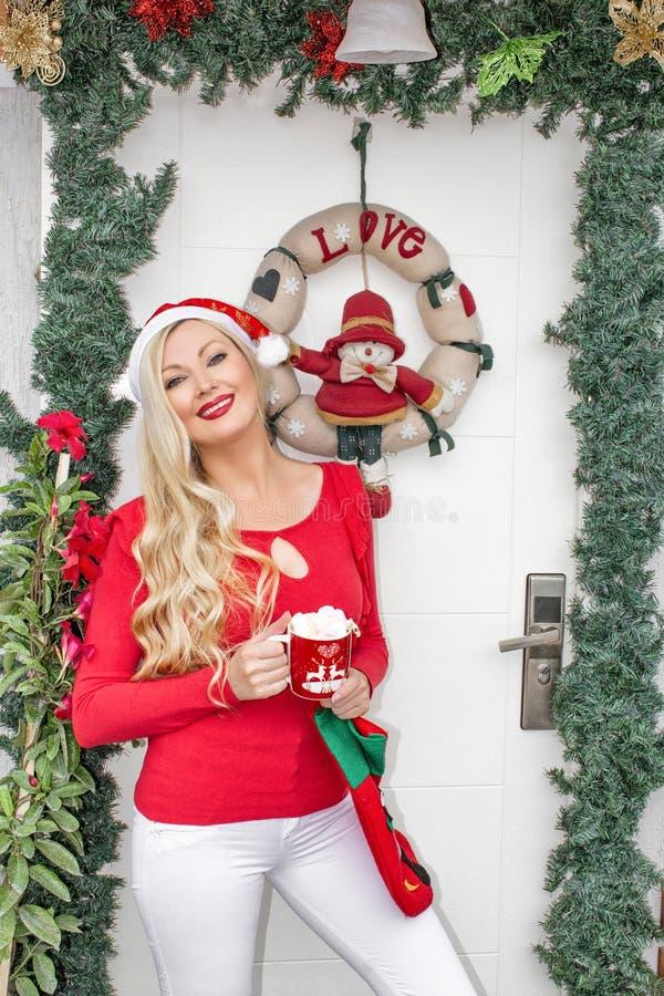 Piękna młoda blondynki dziewczyna w Santa nakrętki stojakach przy dzwi wejściowy dekorującym z wiankiem i gałąź świerczyna zdjęcia royalty free