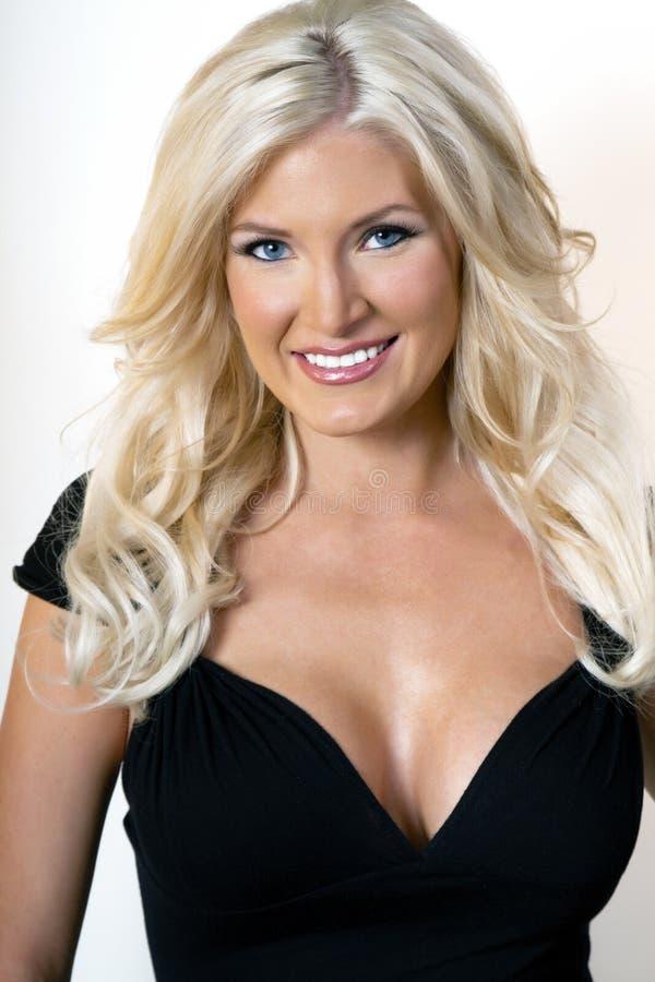 Piękna młoda blondynki kobieta w czerni sukni obrazy stock