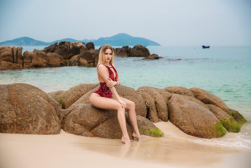 Piękna młoda blondynki kobieta w czerwonym bikini pozuje na plaży Seksowny wzorcowy portret z perfect ciałem Pojęcie lato zdjęcie royalty free