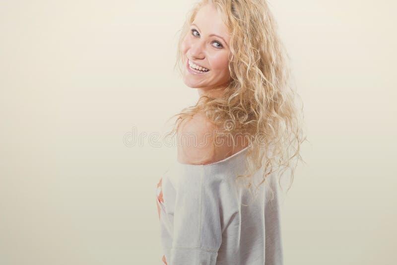 Piękna młoda blondynki kobieta w kamizelce i cajgach na białym tle obrazy stock