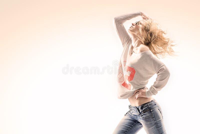 Piękna młoda blondynki kobieta w kamizelce i cajgach na białym tle z energicznym tanem rusza się obrazy royalty free