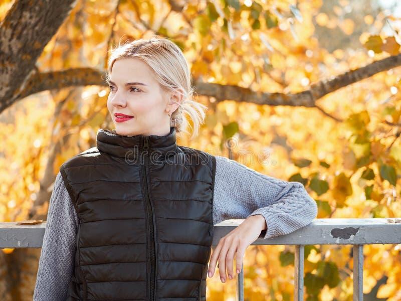 Piękna młoda blondynki kobieta w przypadkowym stroju pozuje przy miasto parkiem, jesień liści tło zdjęcia stock