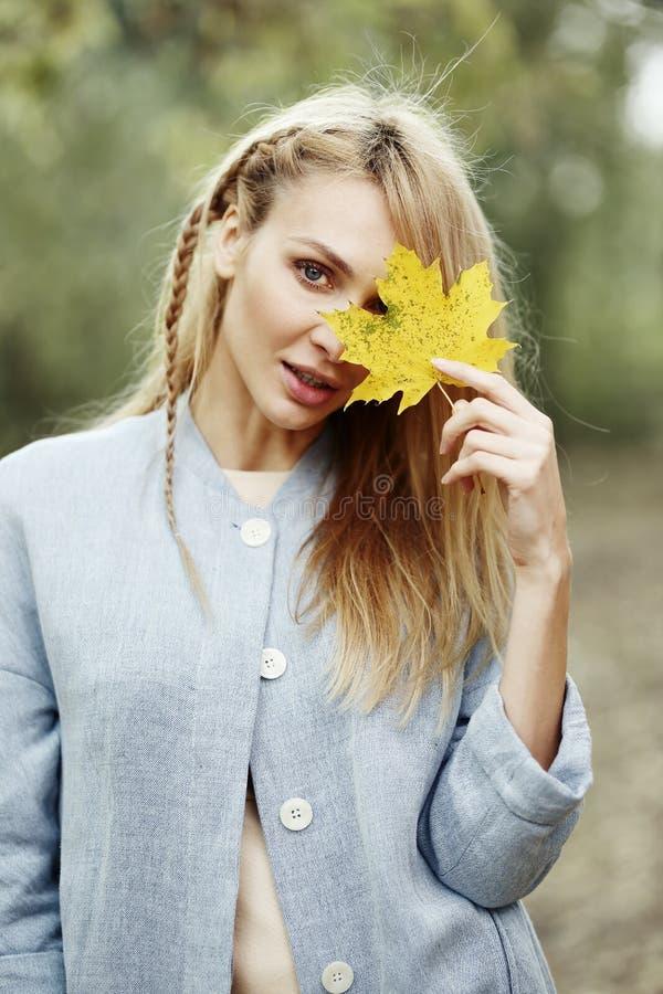 Piękna młoda blondynki kobiety nakrycia twarz z żółtym liściem, jesieni pojęcie obrazy stock