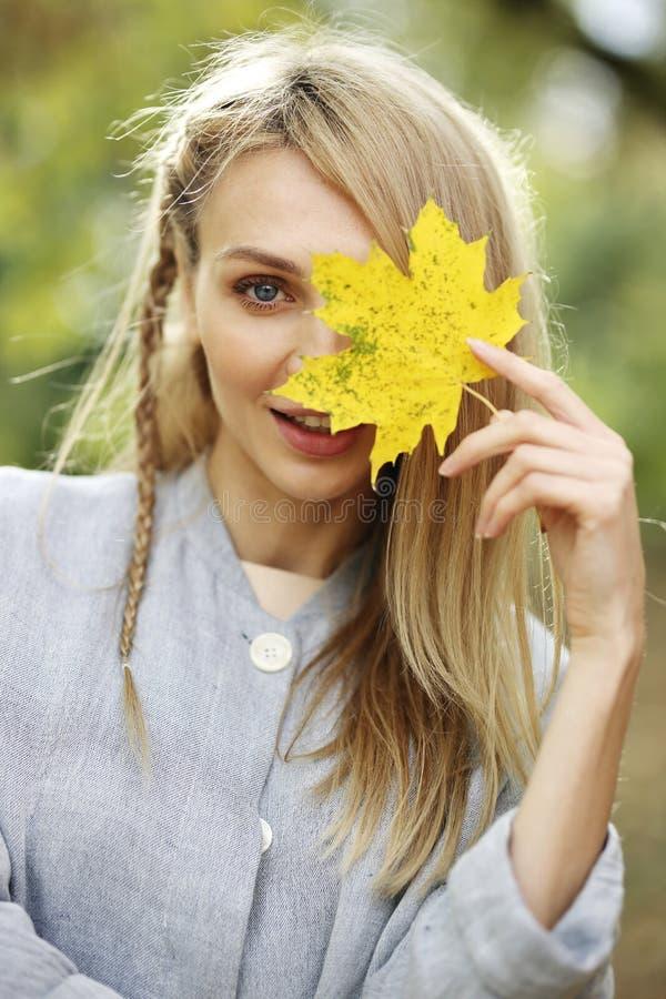 Piękna młoda blondynki kobiety nakrycia twarz z żółtym liściem, jesieni pojęcie obraz stock