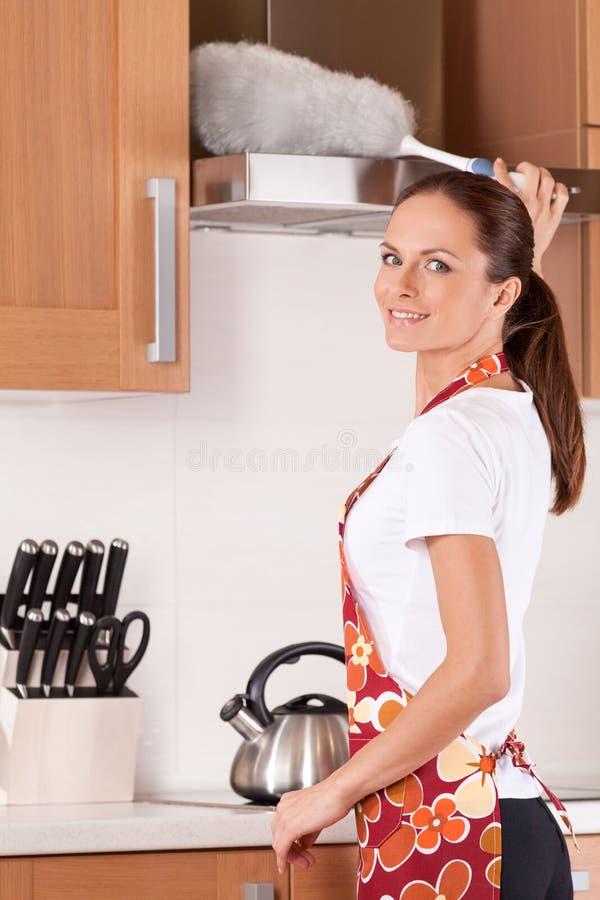 Piękna młoda brunetka czyści kuchnię. obraz royalty free