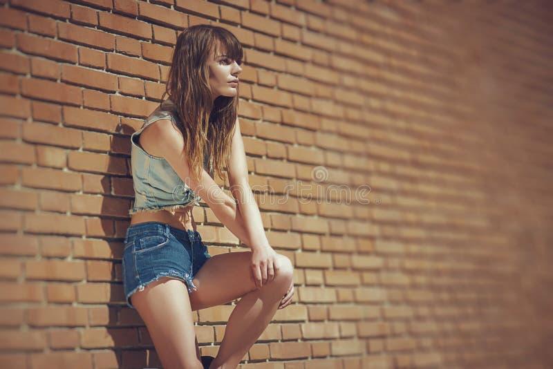 Piękna młoda brunetka w cajgach odziewa pozować plenerowego pobliskiego czerwonego ściana z cegieł obrazy stock