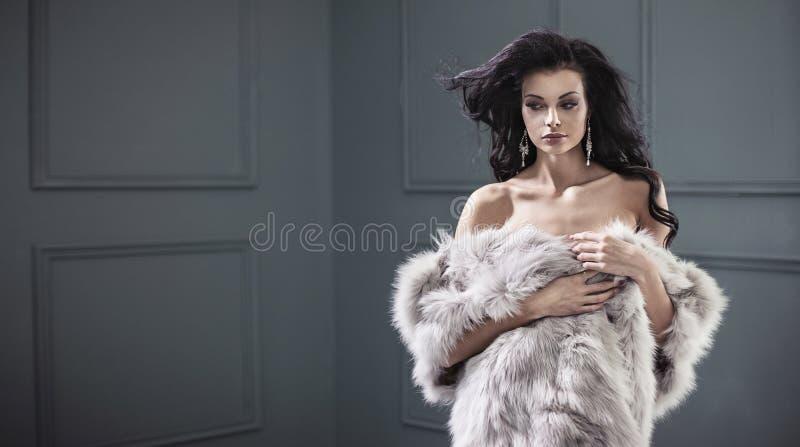 Piękna młoda brunetki dama jest ubranym eleganckiego futerkowego żakiet fotografia royalty free