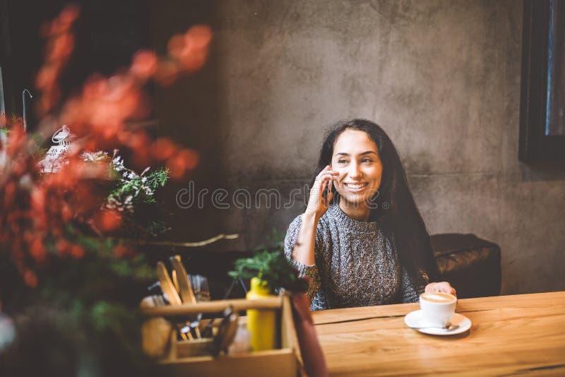 Piękna młoda brunetki dziewczyna opowiada na telefonie komórkowym przy drewnianym stołowym pobliskim okno i pije kawę w kawiarni  obraz royalty free