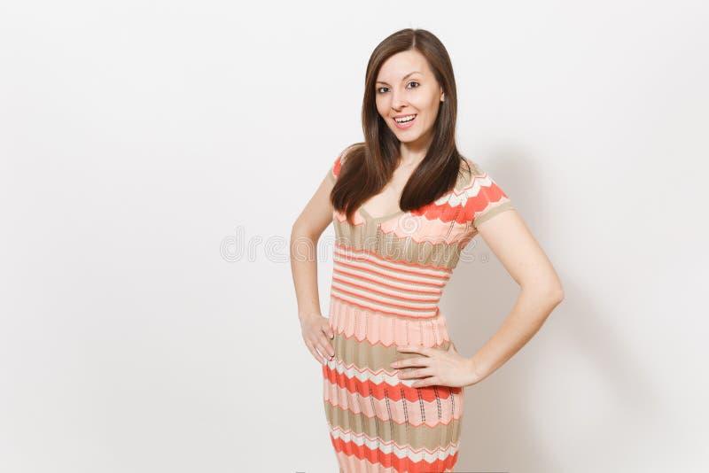 Piękna młoda brunetki dziewczyna w lekkiej beżu i menchii wzorzystości sukni raduje się, uśmiechający się rękę wewnątrz i trzymaj fotografia stock