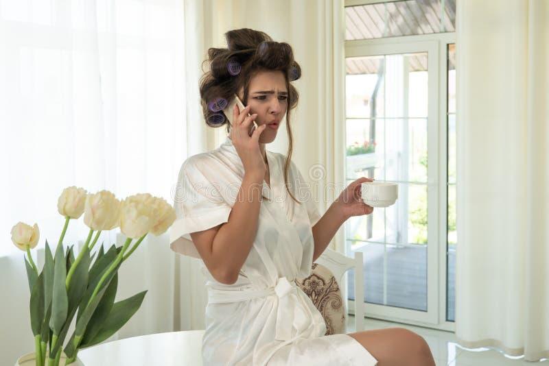 Piękna młoda brunetki kobieta mówi na smartphone w włosianych curlers podczas gdy siedzący na stole i trzymający filiżanka kawy obrazy stock