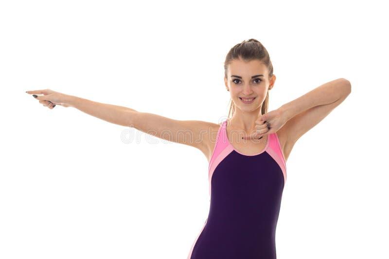 Piękna młoda brunetki kobieta w ciała swimsuit pozuje i ono uśmiecha się na kamerze odizolowywającej na białym tle zdjęcia royalty free