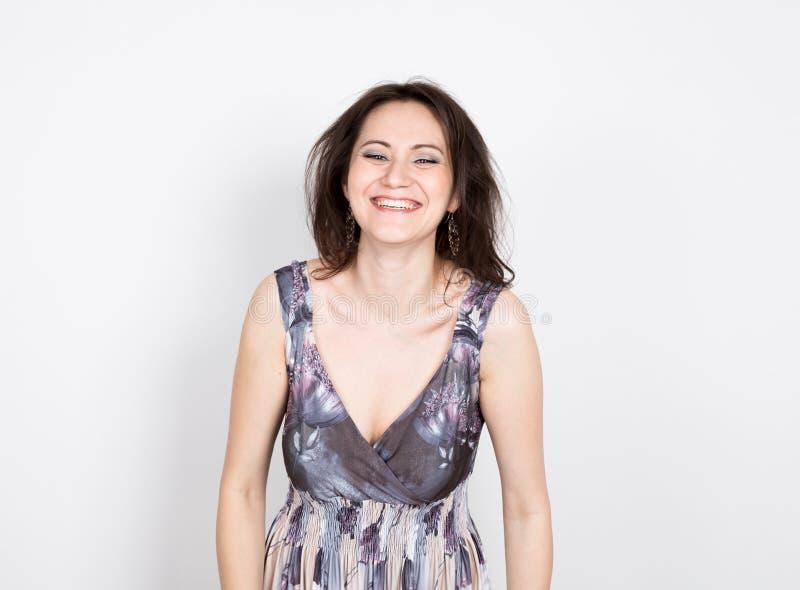 Piękna młoda brunetki kobieta w kolorowej sukni pozuje i wyraża różne emocje radość, śmiech zakończenia portret zdjęcie stock