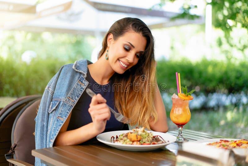 Piękna młoda caucasian kobieta je świeżej Caesar sałatki w plenerowej restauracji Lato nastrój, cieszy się jedzenie zdjęcie royalty free