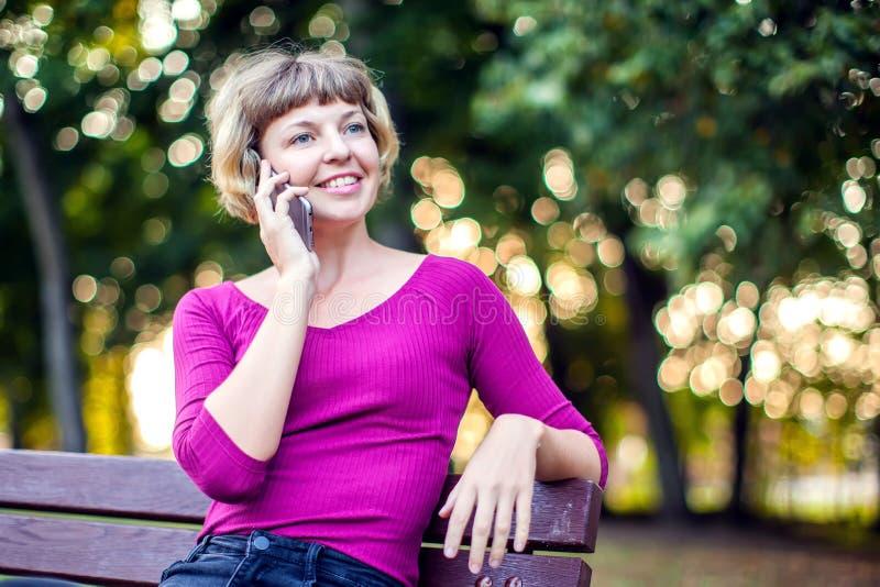 Piękna młoda caucasian kobieta używa jej ono uśmiecha się i smartphone zdjęcia royalty free