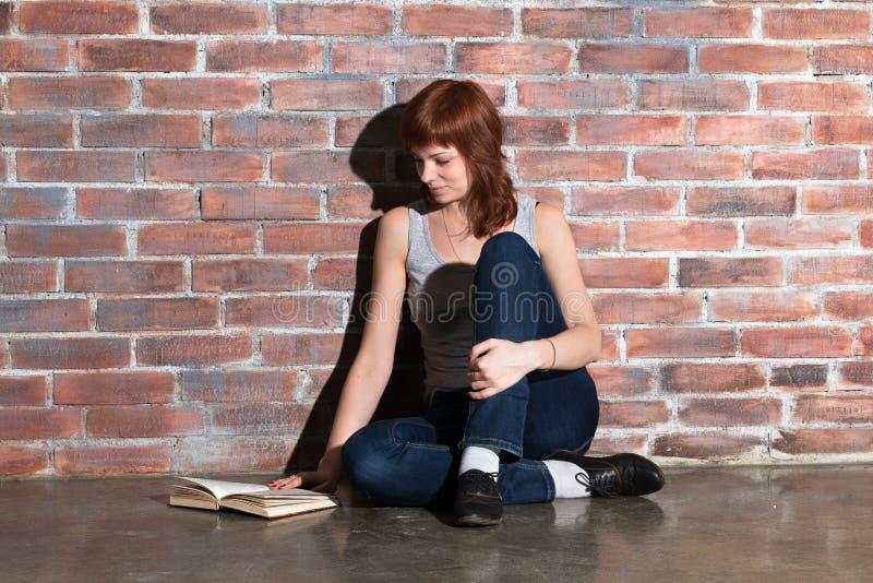 Piękna młoda czerwona włosiana kobieta w cajgach z książkowym obsiadaniem na podłogowym pobliskim ściana z cegieł Attentively czy zdjęcie royalty free