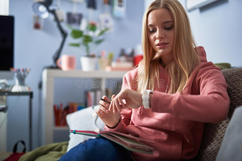 Piękna młoda dama patrzeje jej wristwatch w różowym hoodie zdjęcia royalty free