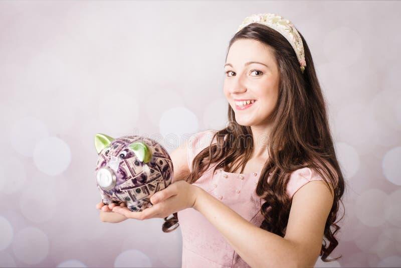 Piękna młoda dama trzyma USA banknoty i prosiątko banka zdjęcie royalty free
