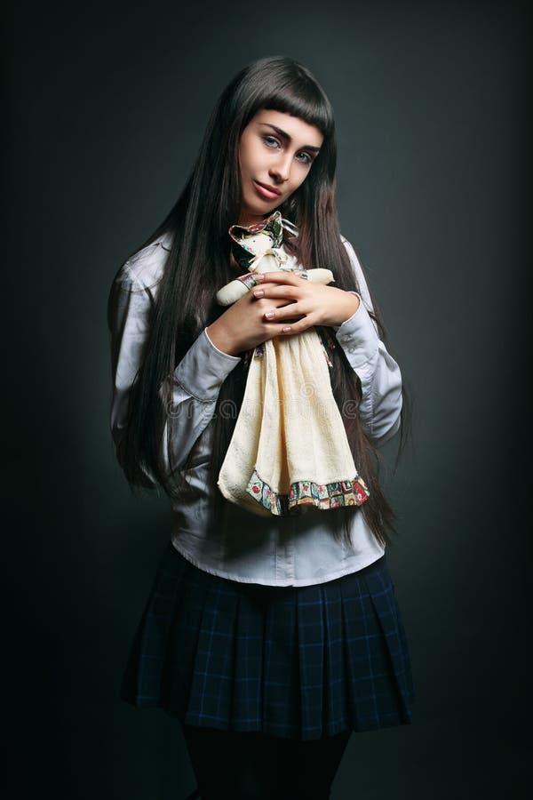 Piękna młoda dziewczyna ściska lalę zdjęcia royalty free